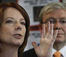 Julia Gillard speaks with her hand held up, Kevin Rudd's face is in the background