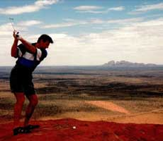 Football celebrity Sam Newman poses with a golf ball on top of Uluru, he appears poised to strike the ball with a golf club