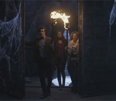 The Doctor, Amy Pond and River Song are walking through an underground space.  The Doctor is leading, holding a flaming torch.  There are stone walls and enormous cobwebs.