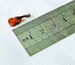 "Tiny violin/fiddle less than half an inch long ""Chen, of Beijing, China, took seven years to craft the tiny instrument from 30 separate parts with strings thinner than a human hair."""