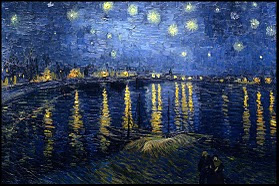 The night lights of a town are reflected in the waters of a river.  Above the town the sky is filled with brightly shining stars.