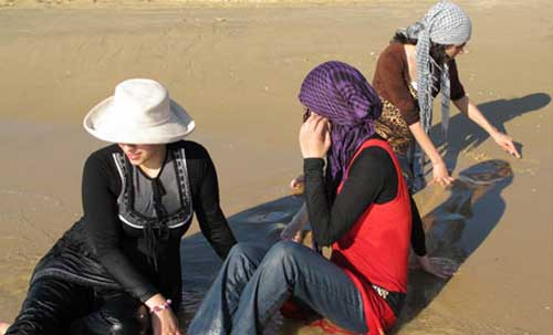 3 women sit in very shallow waves at the edge of the sea