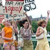 Women looking excited and cheerful while holding protest placards demanding Equal Pay