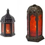 two lanterns with red glass covering glowing candels