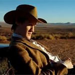 The Doctor played by Matt Smith is lounging on a car bonnet/windscreen in the American West, wearing a cowboy hat