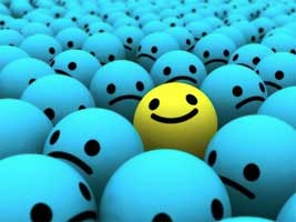 A sea of blue balls with sad faces surrounds one yellow ball with a smiley face