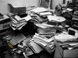 A pile of manuscripts burying just-perceived office furniture