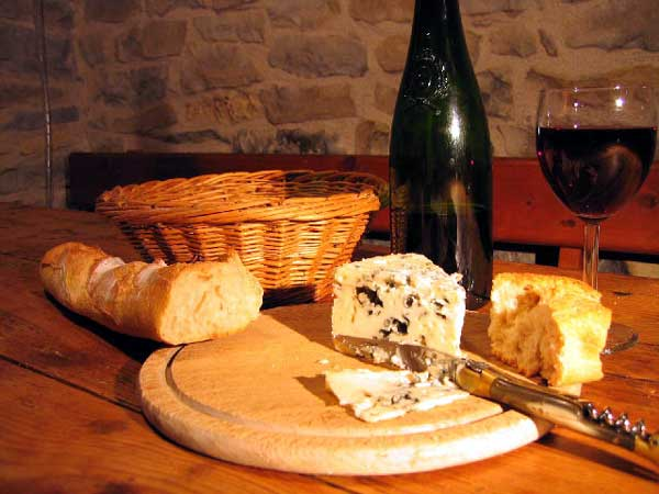 A wedbe of Roquefort cheese on a board, accompanied by crusty bred and red wine