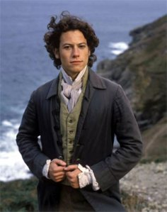 Ioan Gruffudd stands on a windswept clifftop with his back to the crashing sea, wearing Regency period costume