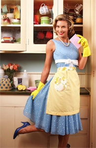 A slender pale-skinned woman, hair styled and made up, wearing a 50s style dress with pearls, high heels, lacy apron and rubber gloves, poses in front of kitchen cabinets holding a sponge in one hand. One leg is lifted up and she is holding her dress in a coquettish display.