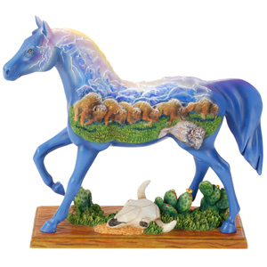 A ceramic horse figurine painted bright blue with its flanks decorated with a depiction of a herd of bison.  Beneath it lies the skull of a cow.