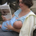 A pale skinned woman reads 'Breastfeeding: A Parent's Guide' while nursing a baby