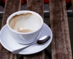 A coffee cup, almost empty, sits on a saucer with a spoon. It's resting on the slats of a wooden table. Image by doug88888 on flickr; used with a Creative Commons license.