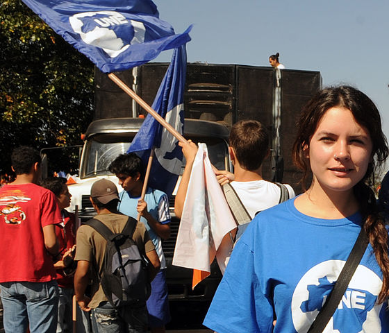 A young woman with pale skin and dark hair is in the left foreground, wearing a blue T-shirt with a white logo, behind her are many other students waving flags and marching