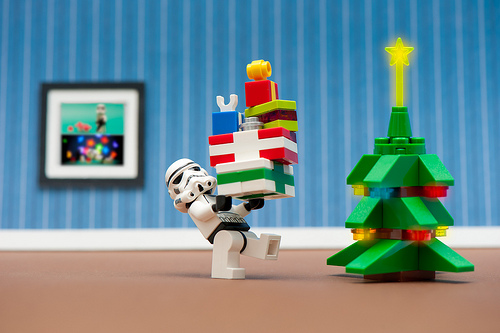 Lego Stormtrooper carries Lego presents to a Lego Christmas tree