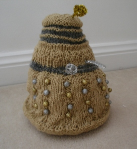 A gold Dalek with silver accents and gold and silver beads as its bobbles. The plunger and ray gun are made of a silver pipecleaner, and the eyestalk out of a gold one.
