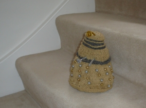 A gold Dalek with silver accents and gold and silver beads as its bobbles. The plunger and ray gun are made of a silver pipecleaner, and the eyestalk out of a gold one. The Dalek is posed on some stairs.