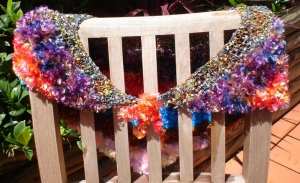 Hanging on a chair, a multicoloured shawl or shrug with a tie in front with reddish tones. The top part is a spidery rainbow wool, followed by feathery wools in purple tones, then red, blue, brown, and pink.
