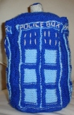 A knitted toy TARDIS, in dark blue with light blue detailing and white lettering.