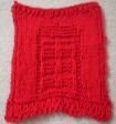 A red dishcloth with a TARDIS pattern on it.