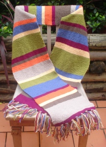 A long and while multicoloured scarf with tassels arranged on a chair in an outdoor setting.