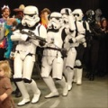 A line of fans in stormtrooper costumes dancing the conga