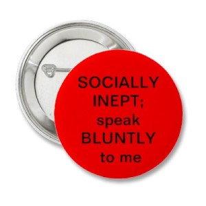 A pinback badge: red background with text saying SOCIALLY INEPT; speak BLUNTLY to me