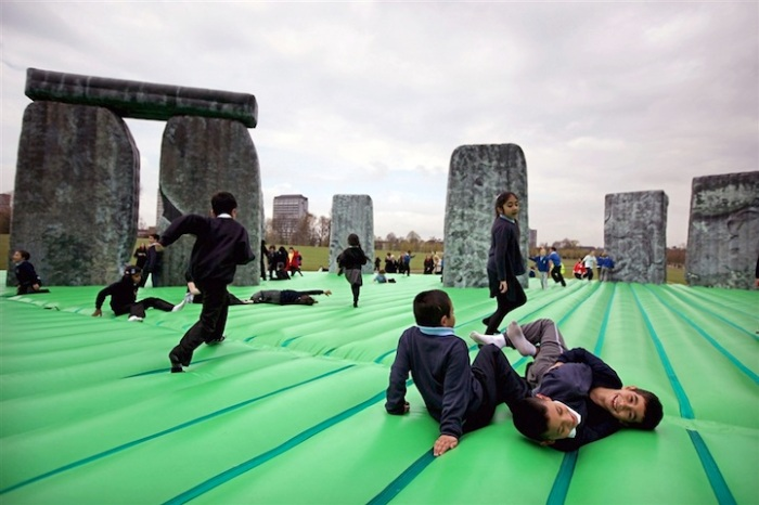 An inflatable bouncy sculpture of Stonehenge full of happy kids