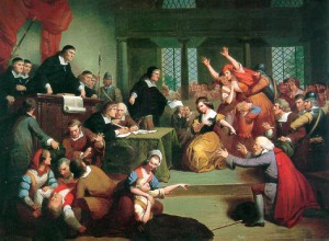 A painting of a court scene in which several women in Puritan dress point, raise their arms, or collapse on the floor. Two black-robed judges and several citizens look on.