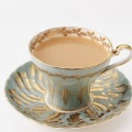 Cup of tea in blue-grey and gold fine china.