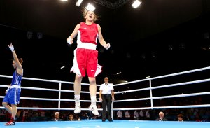 Katie Taylor in centre of boxing ring, jumping with joy, watched by her opponent and referee.