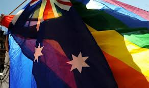 a silhouetted figure holding two flags - the australian flag and the rainbow flag