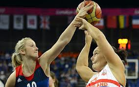 A mid-torso to head-shot of two pale-skinned women athletes in wheelchairs competing for possession of the basketball