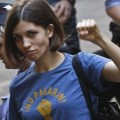 Tolokonnikova, wearing a blue t-shirt with a political slogan, raises a fist, while leaving court..
