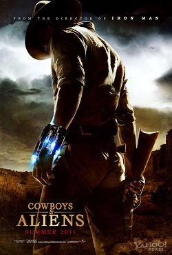 A man stands in desert canyon territory wearing Wild West costume (gunbelt, hat, chaps) under a dark and threatening sky.  He is shown from behind, half-turning, holding a rifle in one hand and wearing a metal cuff with blue laser lights on his other wrist