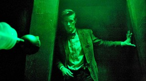 An eerily green-cast shot of a very apprehensive eleventh Doctor standing in a doorway - on screen-left we can just see the outline of the eye-stalk of a Dalek