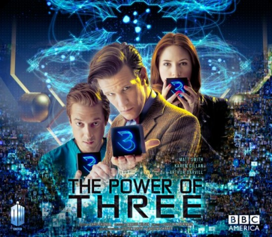 The Doctor, Amy and Rory are standing together, holding small black cubes which each have a glowing number 3 on the side facing forward - the background looks like a window onto space at the top and fades into a mysterious pixellated background at the bottom