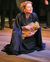 A middle-aged white woman in a black cloak kneels, holding a baby wrapped in brown cloth.
