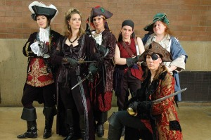 Group of six white women in various approximations of 18th century pirate costume.
