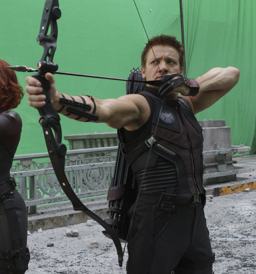 Production photo of Jeremy Renner drawing Hawkeye's bow, in front of a green screen.