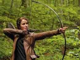 Movie still of Katniss drawing her bow in the woods.