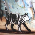 a photo of a stencil-art stripey cat on a brick wall in Newtown