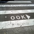Photo of a pedestrian crossing, where there is normally writing that says LOOK with an arrow pointing to the right. The L has been rubbed off so that the sign now says OOK.
