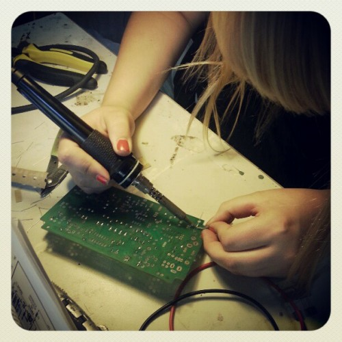 Woman bending over a printed circuit board with a soldering iron