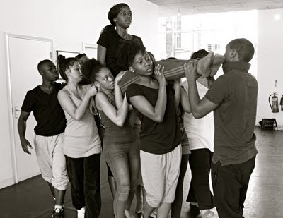 B&W photo of a group of British Afro-Carribean male and female actors in rehearsal clothes, carrying a woman.