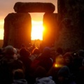 the stone megaliths of Stonehenge host a crowd of people watching the sun rise between two verticals