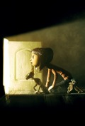 Still from the movie showing Coraline and the black cat peering into a small, lighted doorway.