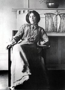 B&W Photo Portrait of Margaret MacDonald, seated in front of a Macintosh-desinged fireplace