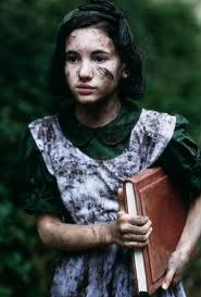 Girl of about 12 in a muddy pinafore, holding a large book.