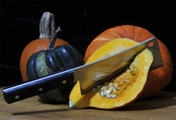 An assortment of pumpkins in different colours.  One has been halved and a cleaver is stuck deeply into its flesh.